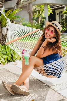 Atractiva mujer joven en vestido azul y sombrero de paja con gafas de sol rosas bebiendo cócteles de alcohol en vacaciones sentado en una hamaca en traje de estilo veraniego, sonriendo feliz en el estado de ánimo de fiesta