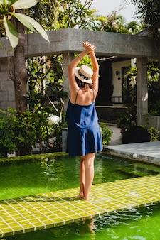 Atractiva mujer joven con vestido azul y sombrero de paja con gafas de sol rosas caminando en la piscina de la villa spa tropical de vacaciones en traje de estilo veraniego, vista desde atrás sosteniendo las manos arriba