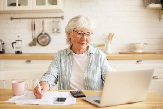 Atractiva mujer madura senior positiva con gafas sentado en la encimera de la cocina frente a una computadora portátil, pagando facturas de gas y electricidad utilizando una aplicación en línea, disfrutando de la tecnología moderna