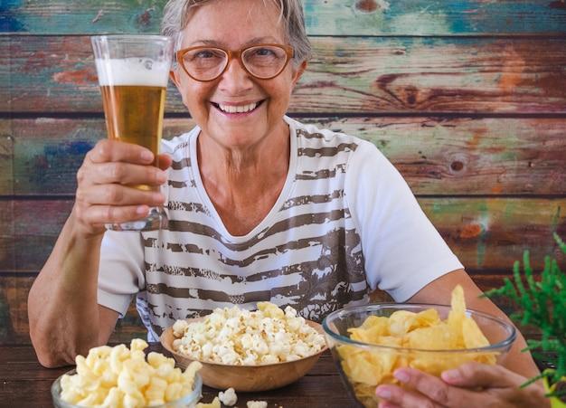 Atractiva mujer mayor sentada en una mesa de madera sosteniendo un vaso de cerveza rubia, mirando a la cámara sonriendo