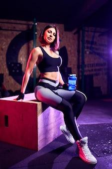 Atractiva mujer de mediana edad con agitador posando en un banco en el gimnasio