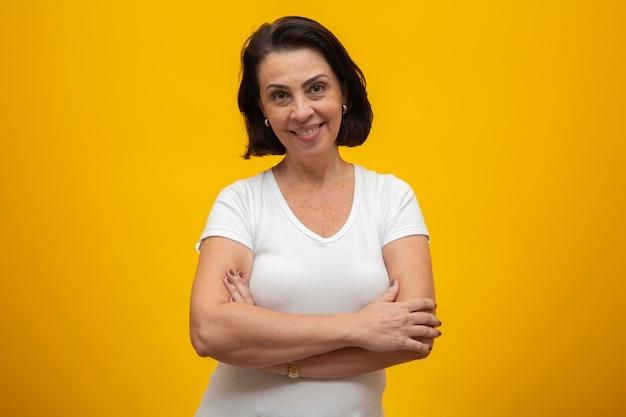 Atractiva mujer de mediana edad con los brazos cruzados sobre amarillo