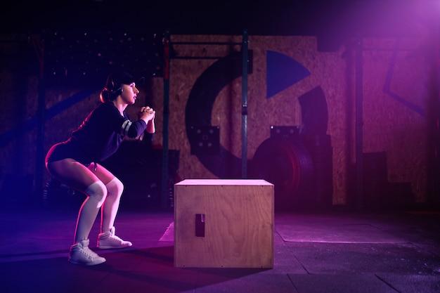 Atractiva mujer de mediana edad en forma haciendo saltos de caja. atleta femenina realiza saltos en el gimnasio