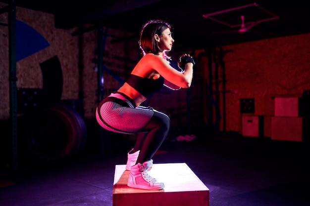 Atractiva mujer de mediana edad en forma haciendo saltos de caja en un estilo de ajuste cruzado. atleta femenina realiza saltos en el gimnasio