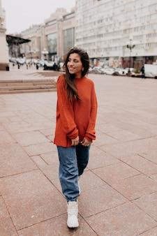 Atractiva mujer moderna caminando por la calle de la ciudad