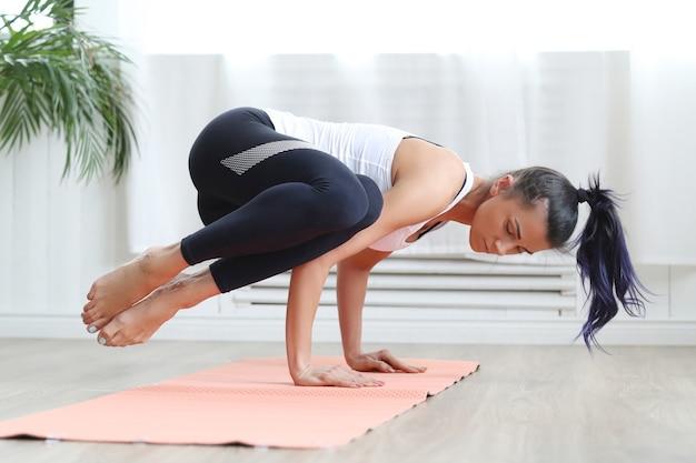 Atractiva mujer morena haciendo yoga en casa.