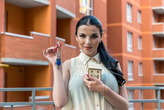 Atractiva mujer morena con llaves y modelo de casa