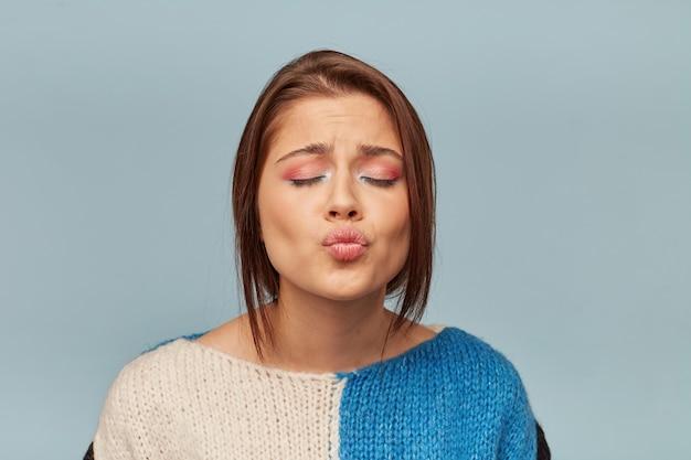 Atractiva mujer morena con maquillaje hermoso muestra beso de aire