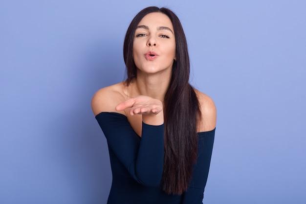 Atractiva mujer morena que sopla beso a la cámara en azul, modelo de mujer joven con elegante vestido posando con hombros desnudos, chica atractiva con piel perfecta y cabello largo y liso