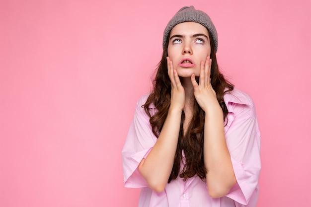 Atractiva mujer morena rizada joven cansada cansada con camisa rosa y sombrero gris aislado en rosa