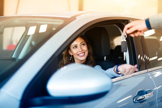 Una atractiva mujer morena sentada en su coche nuevo y tomando las llaves del concesionario de vehículos