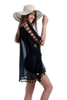 Atractiva mujer morena sonriendo mientras posando en pareo oscuro y traje de baño con sombrero blanco