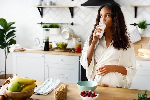 La atractiva mujer mulata sonríe está bebiendo leche cerca de la mesa con frutas frescas en la moderna cocina blanca vestida con ropa de dormir con el pelo suelto y mirando a la derecha