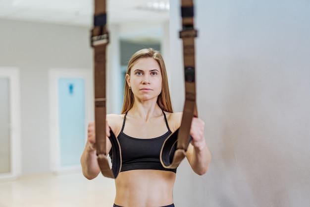 Atractiva mujer muscular haciendo flexiones entrenando brazos con correas de fitness trx en el gimnasio.