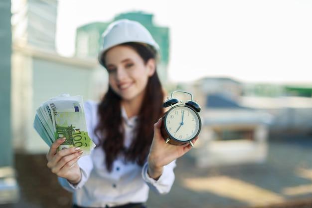 Atractiva mujer de negocios con blusa blanca, casco y falda negra se paran en el techo y guardan dinero y despertador