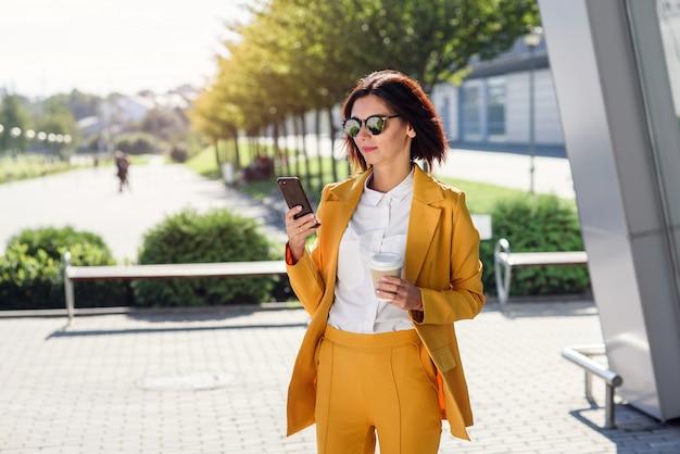 Atractiva mujer de negocios en gafas de sol y traje amarillo caminando cerca del centro de la oficina con una taza de café y utiliza smartphone. concepto de estilo de vida y éxito empresarial. almuerzo entre días laborables.