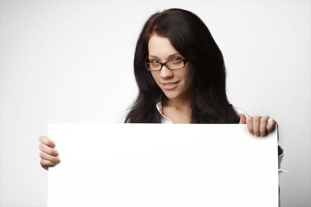 Atractiva mujer de negocios morena asomándose por encima de una pancarta