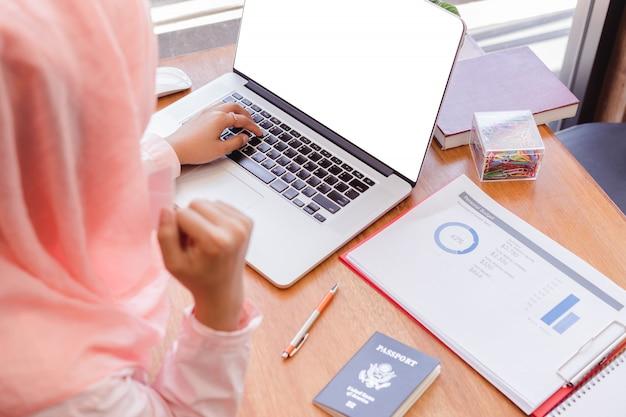 Atractiva mujer de negocios musulmán usa alcanza objetivos. portátil con pantalla en blanco