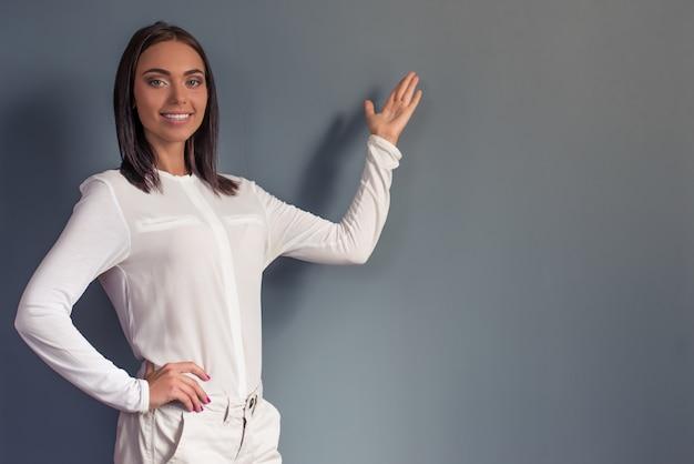 Atractiva mujer de negocios está de pie sobre fondo gris con copyspace