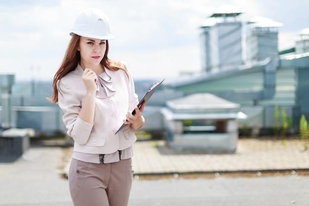 Atractiva mujer de negocios en traje beige pararse en el techo y sostener la tableta