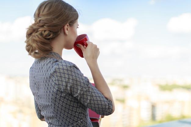 Atractiva mujer de negocios con un vestido estampado de pie en el techo y sostiene la carpeta de papel y la taza roja
