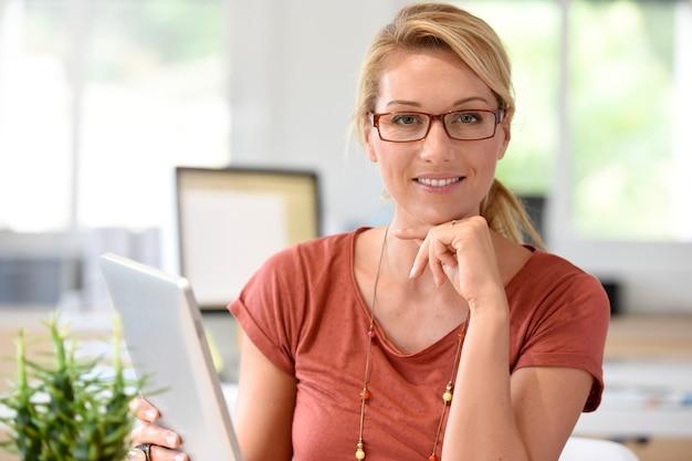 Atractiva mujer de oficina en casa trabajando en tableta digital.