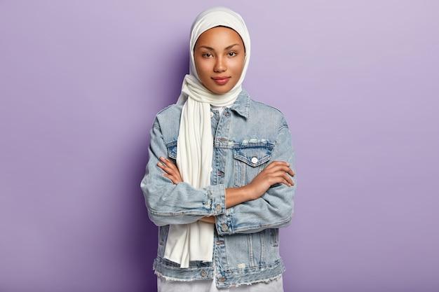 Atractiva mujer oriental se cubre la cabeza con un pañuelo blanco para proteger su dignidad y poder, tiene un código de vestimenta especial, mantiene las manos cruzadas, mira con modestia, posa sobre una pared morada. reglas islámicas