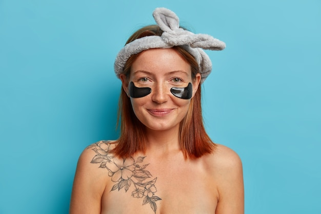 Atractiva mujer pecosa con peinado bob, usa diadema, aplica parches humectantes de hidrogel de colágeno debajo de los ojos, disfruta del procedimiento de cuidado de la piel, posa desnuda, muestra su tatuaje, sonríe agradablemente