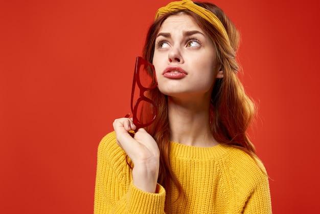 Atractiva mujer pelirroja con gafas rojas suéter amarillo ropa casual estilo de vida estilo callejero
