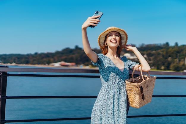 Atractiva mujer pelirroja posando en un día soleado haciendo selfie con teléfono camina por el muelle cerca del ...