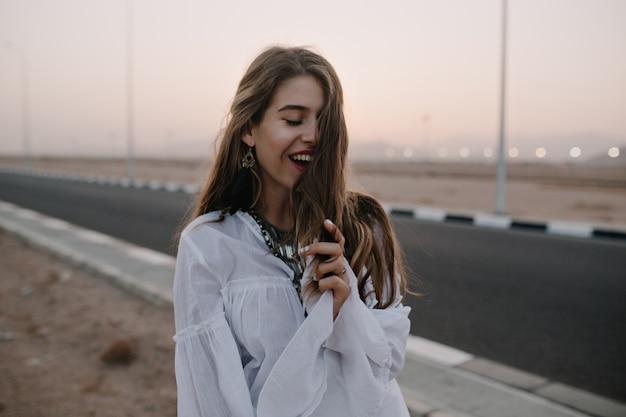 Atractiva mujer de pelo largo sonriente posando con los ojos cerrados mientras camina por la calle en las noches de verano. retrato de hermosa joven feliz en túnica disfruta de vacaciones y pasar tiempo afuera