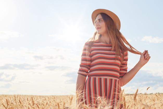 Atractiva mujer de pie en el campo de trigo, sosteniendo su cabello con las manos