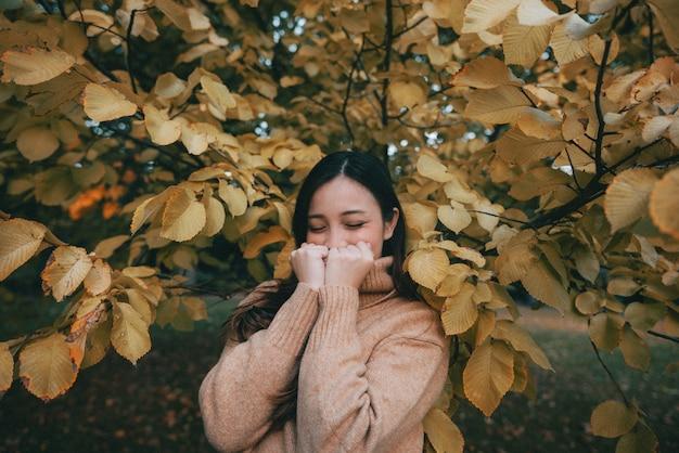 Una atractiva mujer de pie cerca de un hermoso árbol con hojas doradas