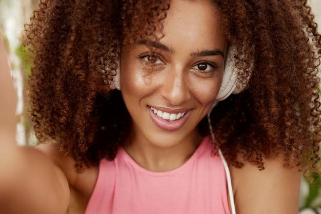 Atractiva mujer de piel oscura con cabello oscuro rizado y tupido, usa audífonos, escucha audiolibros, muestra una sonrisa agradable, hace selfie, disfruta del tiempo libre. estudiante descansa después de las lecciones universitarias