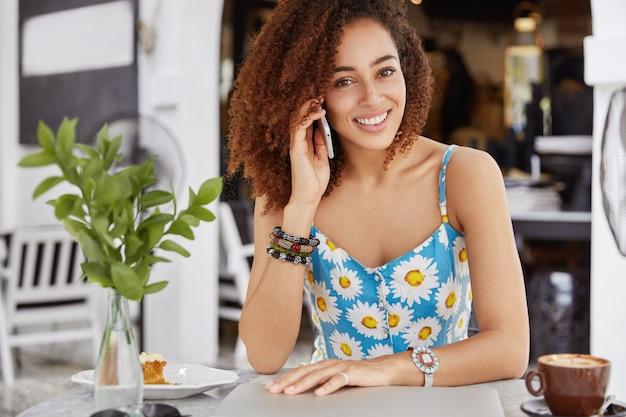 Atractiva mujer de piel oscura tiene conversación telefónica en un café al aire libre, disfruta de un sabroso pastel y capuchino, comparte las últimas noticias con un amigo.