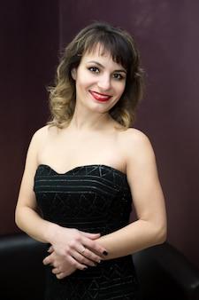 Atractiva mujer posando en vestido negro
