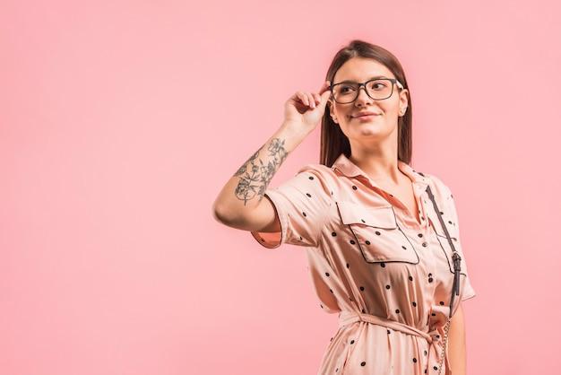 Atractiva mujer positiva en lentes y vestido.