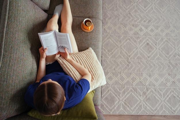 Atractiva mujer positiva leyendo un libro descansando en el sofá