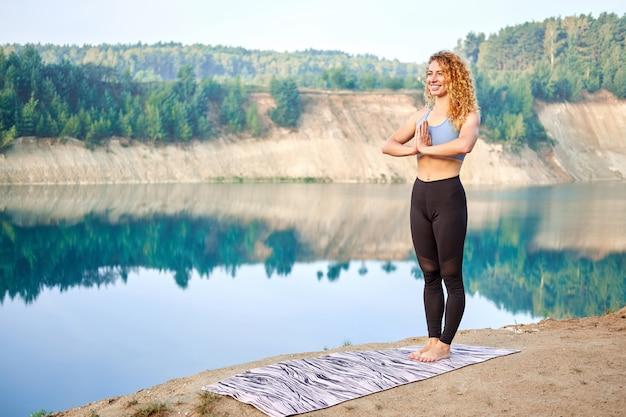 Atractiva mujer rizada pelirroja o modelo practicando yoga al aire libre