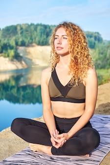 Atractiva mujer rizada pelirroja practicando yoga al aire libre