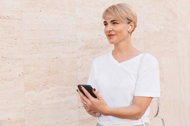 Atractiva mujer rubia con camiseta blanca sosteniendo smartphone, mientras está de pie contra la pared beige al aire libre con auricular inalámbrico