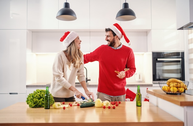 Atractiva mujer rubia cortando pepino mientras está de pie en la cocina con su novio en nochebuena