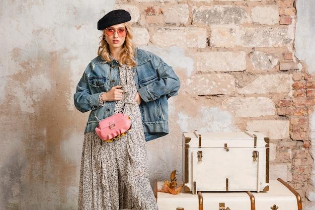 Atractiva mujer rubia con estilo en jeans y chaqueta de gran tamaño caminando contra la pared en la calle