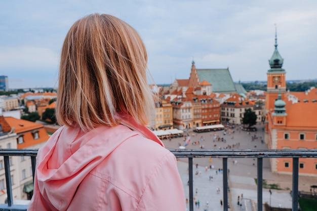 Atractiva mujer rubia mirando el castillo real y el casco antiguo de varsovia, polonia