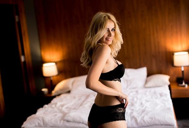 Atractiva mujer rubia en ropa interior negro posando en la habitación de los hoteles