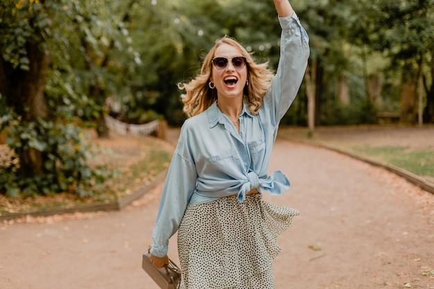 Atractiva mujer rubia sonriente saludando con la mano hola caminando en el parque en traje de verano