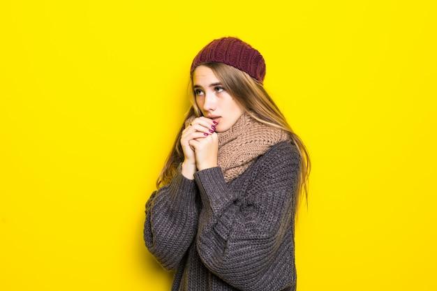 Atractiva mujer rubia en suéter caliente intenta calentar