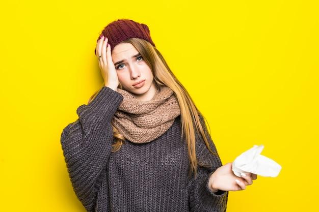 Atractiva mujer rubia en suéter caliente tiene dolor de cabeza e intenta calentar