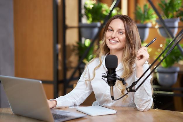 Atractiva mujer sentada en la cafetería y hablando en línea