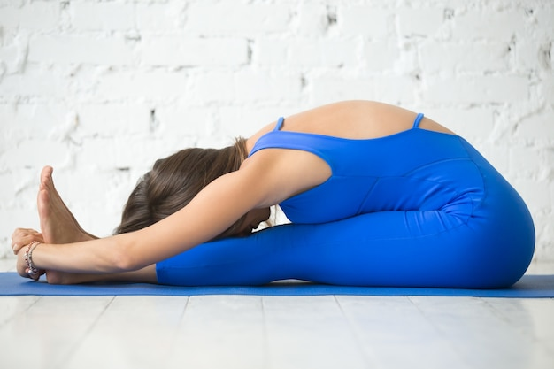 Atractiva mujer sentada delante curva pose, estudio blanco backg